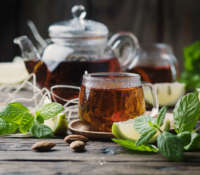 Hot black tea with lemon and mint on the wooden table, selective focus