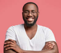 Happy African American male model with dark healthy skin, has broad smile, shows white teeth, keeps hands crossed as demonstrates his confidence, satisfied with result of work, poses indoor.